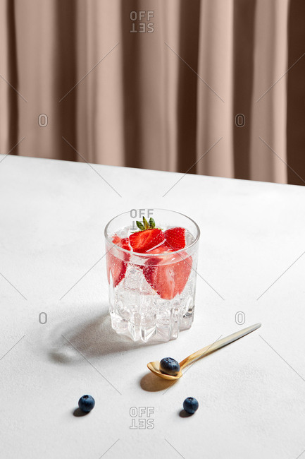 Transparent glass with refreshing strawberry drink and stainless spoon with few blueberries around on white table