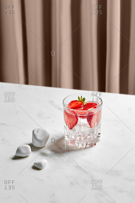 Glass with sliced strawberry, cool water, and a few smooth white rocks