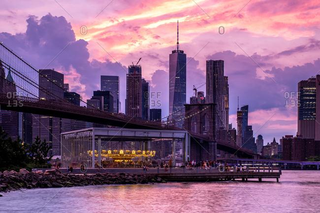 Brooklyn NY - USA - Jun 28 2019: Lower Manhattan skyline and Brooklyn bridge at sunset