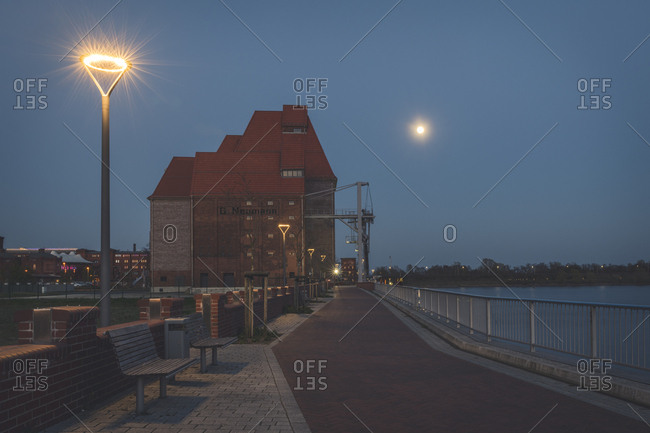 April 18, 2019: Waterfront promenade with old warehouse at night- Wittenberge- Brandenburg- Germany