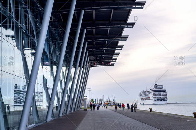 July 6, 2019: Cruise terminal- waterfront promenade and leaving cruise liner- Warnemuende- Rostock- Germany