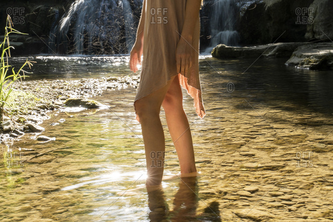 Young woman wading in a natural pool in sunlight- Garrotxa- Spain