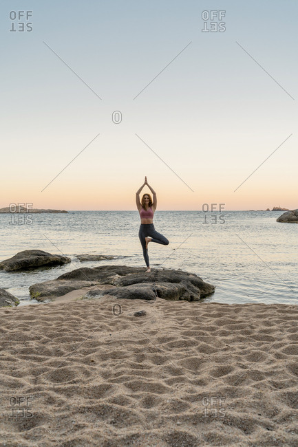 Young woman practicing yoga on the beach- doing tree pose- during sunset in calm beach- Costa Brava- Spain