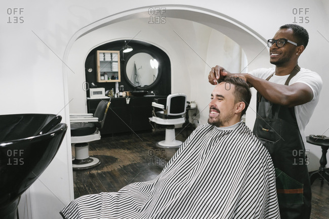 Smiling barber cutting hair of a customer in barber shop