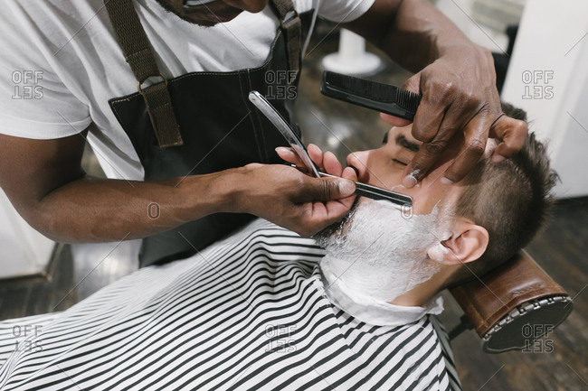 Man getting his beard shaved with razor in barber shop