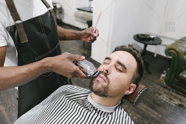 Barber cutting beard of a customer in barber shop