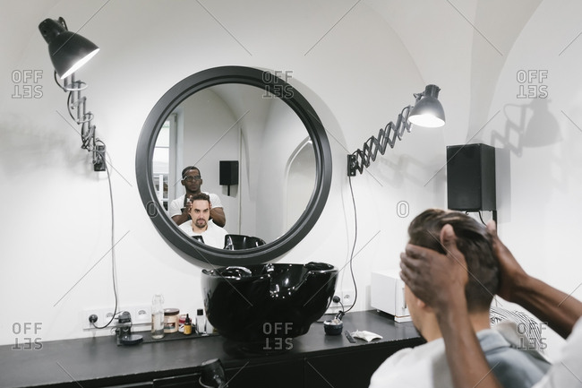 Barber doing hair of a customer in barber shop
