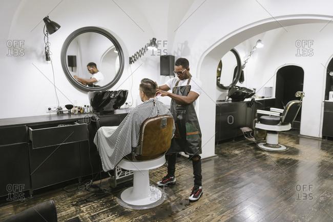 Barber cutting hair of a customer in barber shop