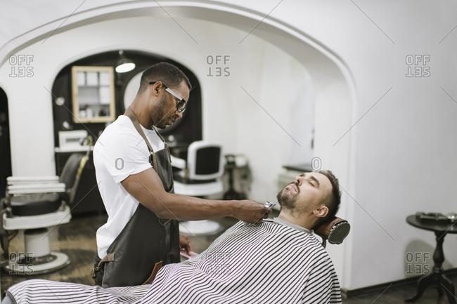 Barber cutting beard of a customer in barber shop