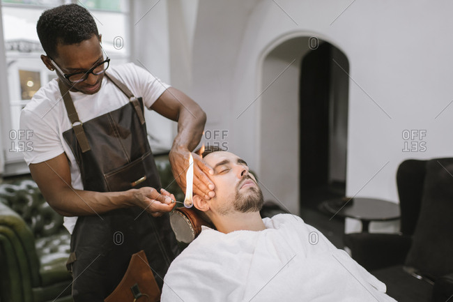 Barber removing ear hair of a customer with fire in barber shop