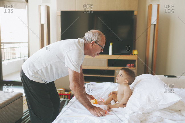 Grandfather playing with a baby at home sticking out tongue