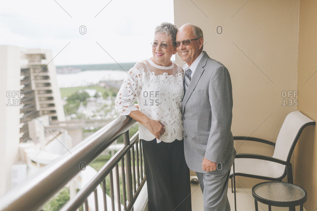 Smiling dressed up senior couple standing on balcony