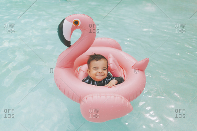 Carefree baby boy in pink flamingo float in swimming pool