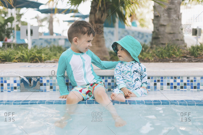 Happy little brothers at a swimming pool