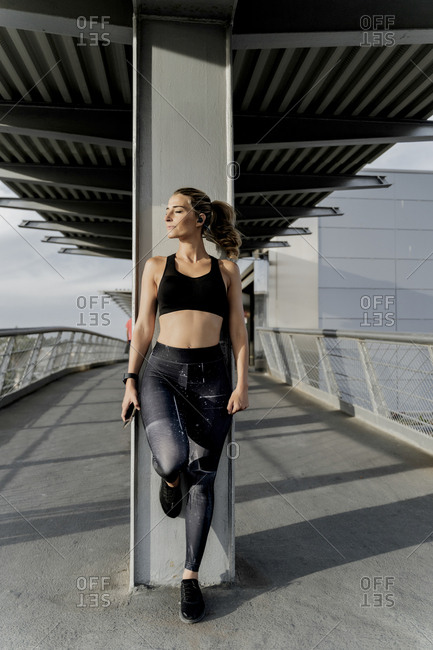 Sporty woman with headphones standing on bridge- listening music- using smartphone