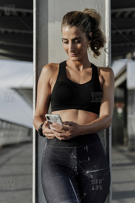 Sporty woman with headphones standing on bridge- listening music- using smartphone