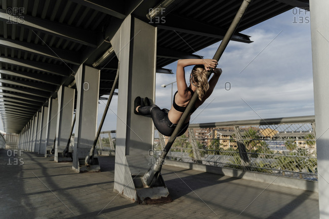Sporty woman working out o a bridge- leaning on bar