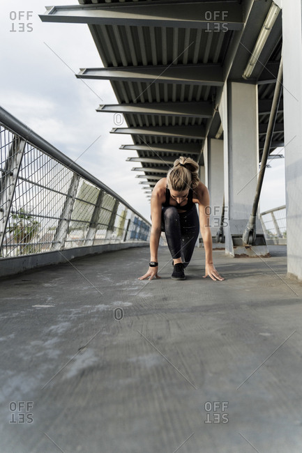 Sporty woman in starting position on a bridge- starting to run