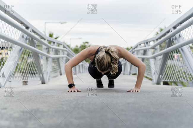 Sporty woman doing push ups- working out on a bridge
