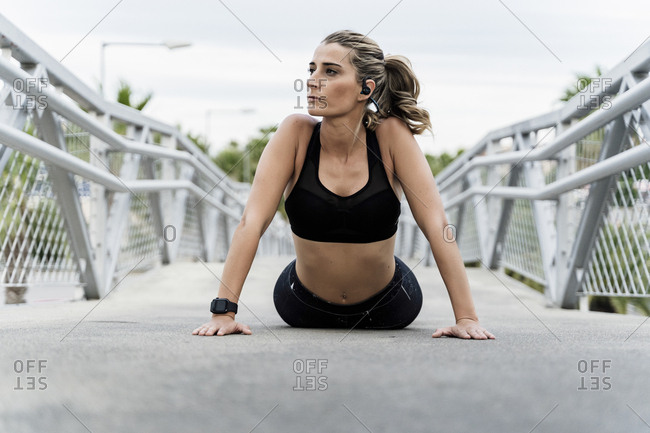 Sporty woman with headphones- working out on a bridge