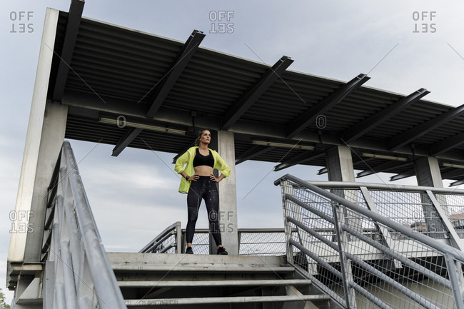 Sporty woman standing on grandstand- looking at distance