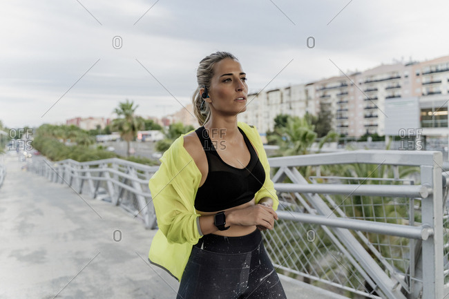 Athlete with earphones and smartwatch on a bridge in the city