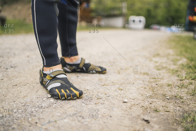 Close-up of man wearing wetsuit and galoshes standing on a path