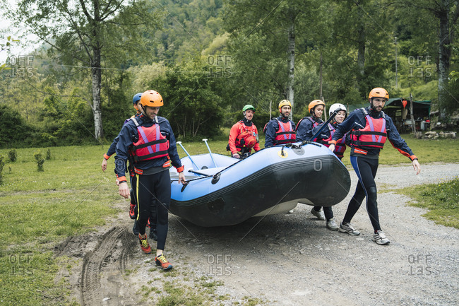 Group of friends preparing for a rafting trip carrying rubber dinghy