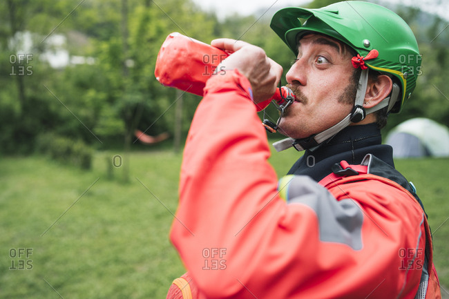 Portrait of a man in protective wear making a funny face drinking from bottle