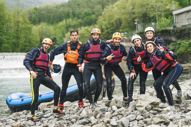 Group of playful friends at a rafting class posing at boat