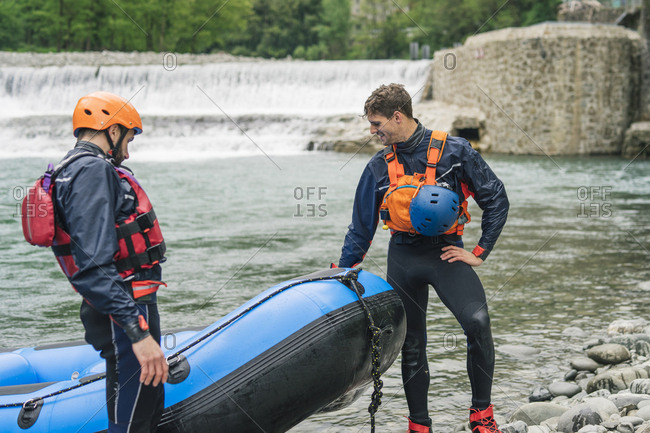 Two men with rubber dinghy at river shore