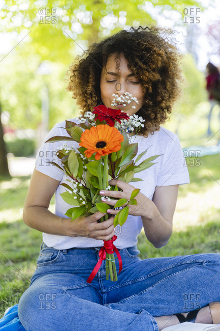 Relaxed woman in park smelling at flowers