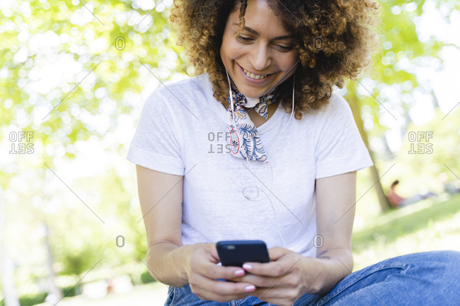 Smiling woman with cell phone and earphones in park