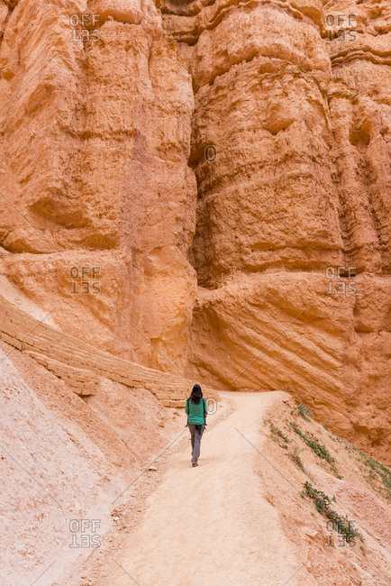 Woman carrying her daughter in a baby carrier walking on path- Bryce Canyon- Utah- USA