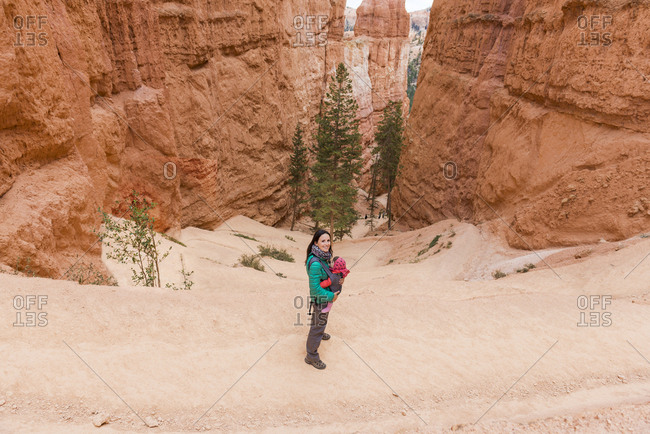 Woman carrying her daughter in a baby carrier at hoodoos in Bryce Canyon- Utah- USA