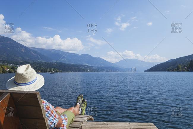 Man resting at lakeshore- Seeboden- Millstatt Lake- Carinthia- Austria