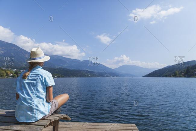 Woman resting at lakeshore- Seeboden- Millstatt Lake- Carinthia- Austria