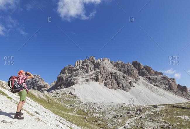 Hiker on hiking trail- Tre Cime di Lavaredo Aera- Nature Park Tre Cime- Unesco World Heritage Natural Site- Sexten Dolomites- Italy