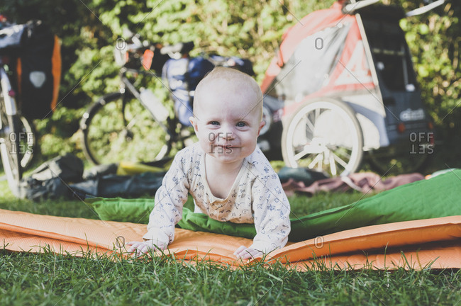 Portrait of happy baby with camping mat in grass