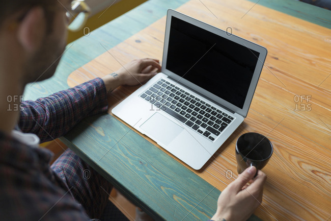 Man wearing pyjama sitting with coffee cup in front of laptop