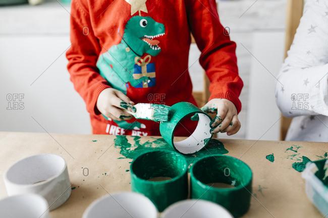 Child doing handicrafts painting rolls of cardboard