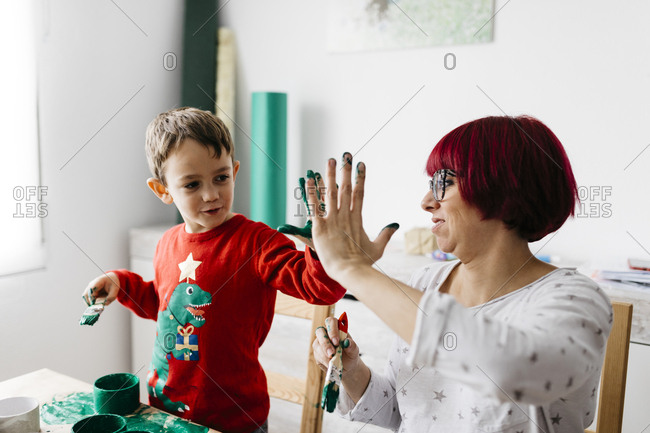 Happy mother and son high fiving while doing crafts at home