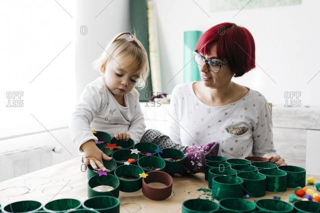 Mother and daughter doing crafts at home with accessories to make a Christmas tree