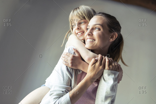 Mother and daughter playing at home- piggyback