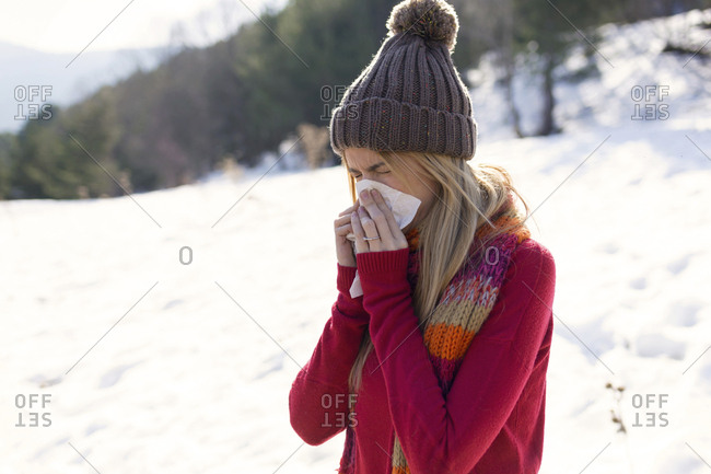 Young blond woman blowing nose in winter