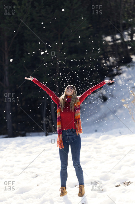 Young blond woman throwing snow in winter