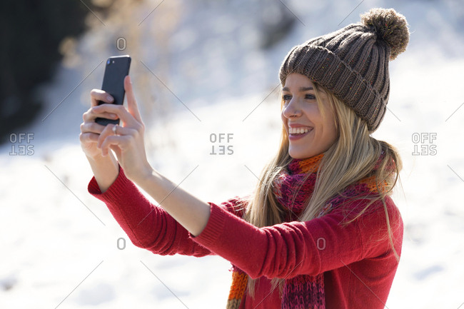 Young blond woman taking a selfie in winter