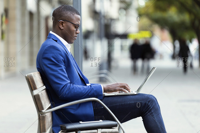 Young businessman wearing blue suit jacket sitting on bench and using laptop