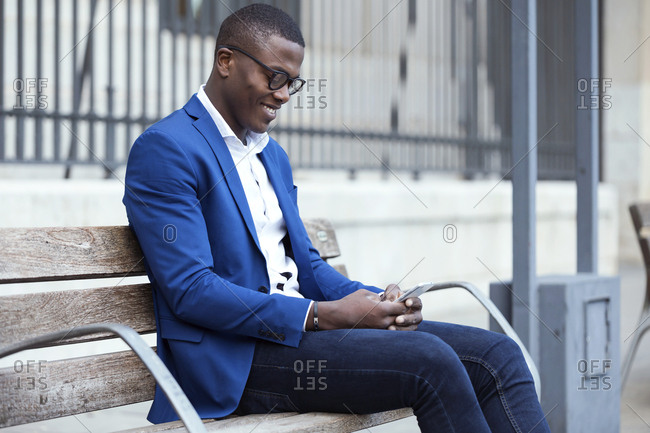 Young businessman wearing blue suit jacket sitting on bench and using smartphone