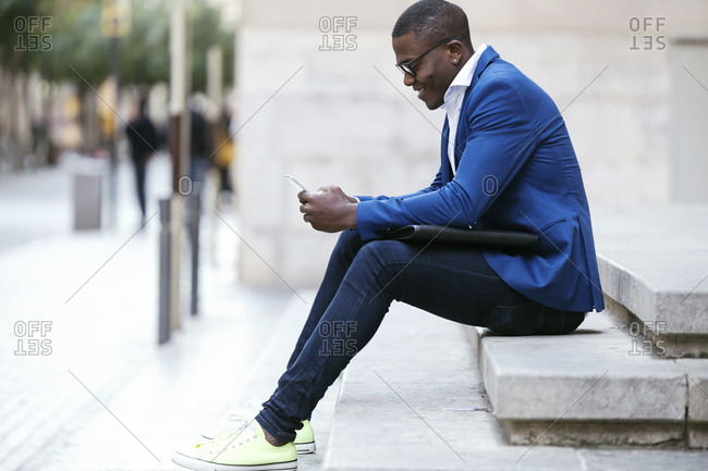 Young businessman wearing blue suit jacket- sitting on step and using smartphone